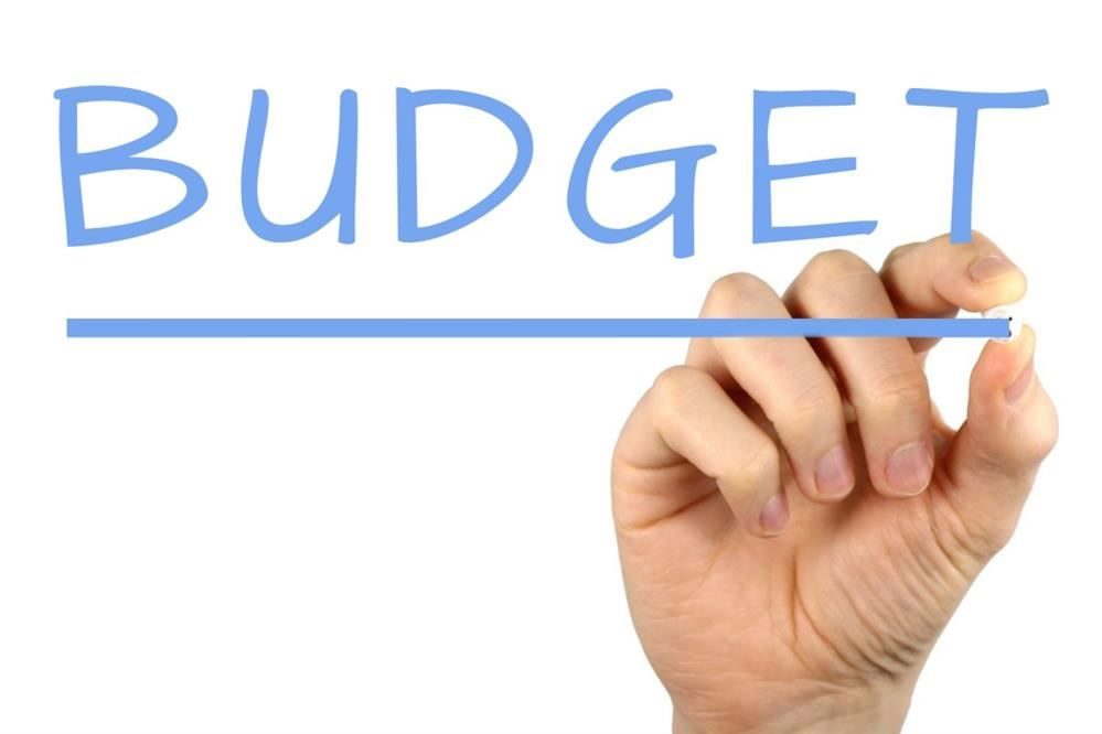 "Clip art image of a hand writing the word ""budget"" on the screen"